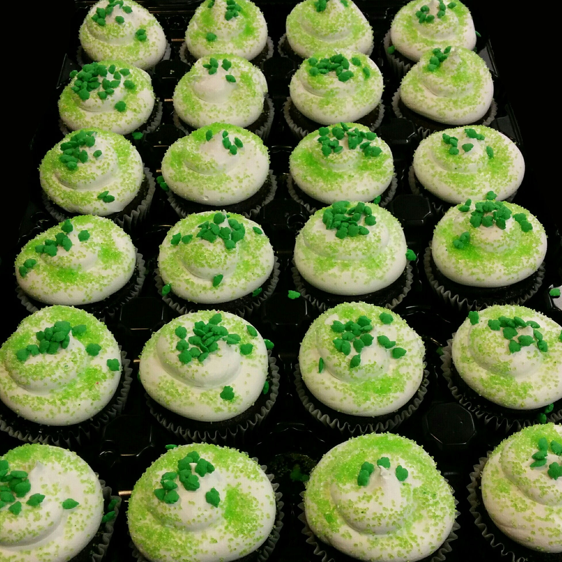 A tray of cupcakes topped with green sprinkles.  Because you can't have a holiday without cupcakes.